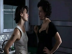 Jennifer Tilly pulling down her bra to showcase lots of