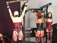 Older man tortures his redead brunette and blonde BDSM slaves on rack