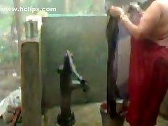 אישה גדולה יפה ההודי גיסה לוקח מקלחת מ משאבת