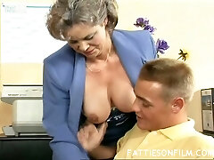 Volutuous grey haired grannie Kelly fucks her young guy in the office