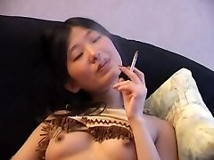 एशियाई धूम्रपान नग्न सोफे पर