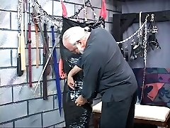 Chunky brunette bdsm slave gets wrapped head-to-toe in black plastic