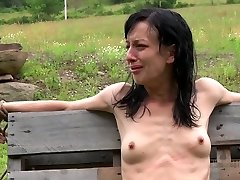 Anorexic dark haired hussy gets her slender bod strapped up to wooden fence outdoors