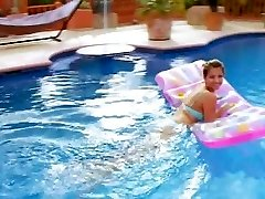 Buxom model tugging in the pool