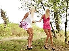 Two hot young blonde girls outdoors make out and get into softcore girl/girl action