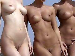 Four beach babes in bathing suits getting naked on the beach