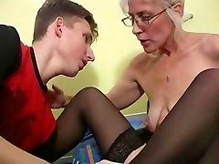 Mature with Platinum Hair Glasses and Stockings Wakes the Boy