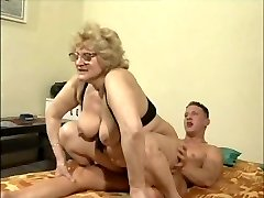 A blonde gran with glasses rides her molten young boy