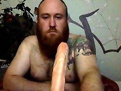Bearded guy Deepthroats gigantic dildo