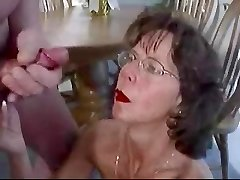 Mature dark-haired in glasses cherishes huge facial cumshot.