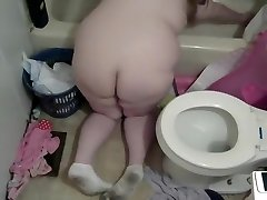 Nude pregnant mom cleaning the shower and toilet
