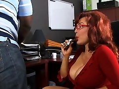 Cute cock sucking redhead takes cumshot from ebony man in office