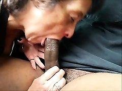 Hungry grandma slurping a big dark-hued cock