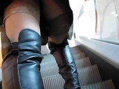 Dívka v černé kožené boty a tan punčochy na eskalátoru