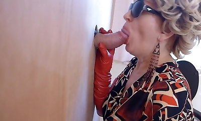 Cougar in boots observes porn and enjoys gloryhole blowjob