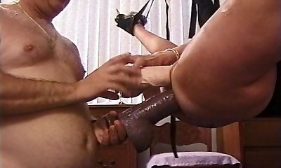 Mature Blonde cockslut in sling stuffed with huge dildos