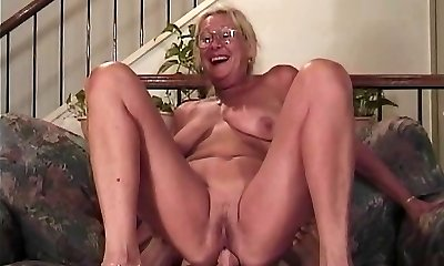 Mature blond with glasses fellates a cock