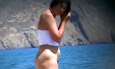 Hot mature beach naturist strips of her clothes and gets wet