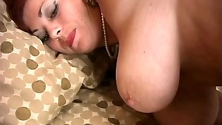 Wonderful buxomy mature redhead plays with a vibrator on the bed
