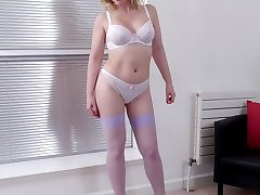 Sexy Milf Jenny shows off her great body in lingerie, silky nylon stockings and tall white...