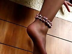 Mischievous chick shows off her embellished feet clad in sheer pantyhose