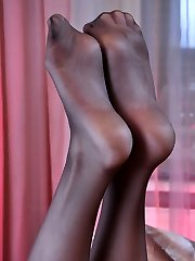 Heated gal takes off stilettos to stroke a rubber toy with her nyloned feet