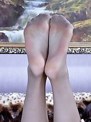 Smoking hot babe takes off her stilettos to massage her aching nyloned feet