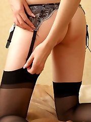 Putting off black plain-top stockings curvy girl preparing to take a shower