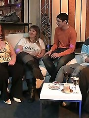 While their friends watch this slender guy and fat chick fuck on the couch and he fists her pussy