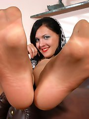Red hot gal squeezing a rubber cock with her cute feet in soft silky tights