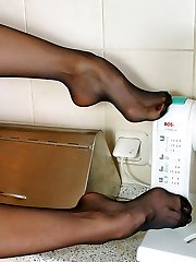 Curly babe in red slip hungrily biting her yummy feet encased in black hose