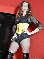 Femdom Strapon Jane plays with her huge strapon cock dressed in fishnets, boots and yellow corset