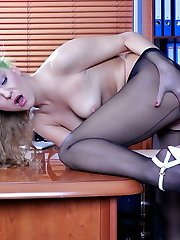Horny secretary in black seamed pantyhose thrusting a huge dildo up her ass