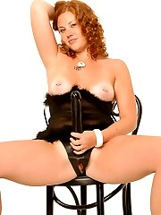 Chubby redhead poses with a strapon dildo sitting on the chair with two guys near her