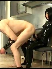 Dark-haired domina in glossy latex catsuit shags her masked slave in the ass