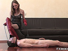 The glossy red boot that Mistress Angela has stuffed into her boy toys face