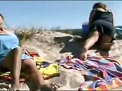 Young man join couple mature lesbians peeing at the beach