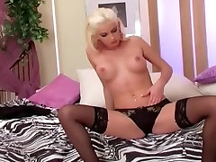 Sexy glamour babe wearing thigh highs and stiletto heels stripping on a bed