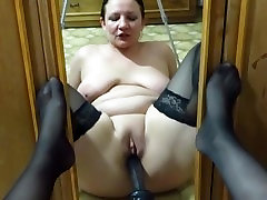 She admires in the mirror as she fucks her holes
