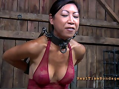 Slender Asian chick is put into shackles in the dungeon