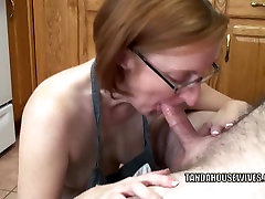 Older floozy Layla Redd is on her knees to engulf a strapon