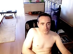 Naughty male is relaxing in the apartment and filming himself on computer webcam