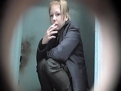 Pretty blonde is smoking and pissing on the toilet