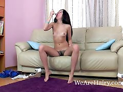 Dalila masturbates on couch with a glass dildo