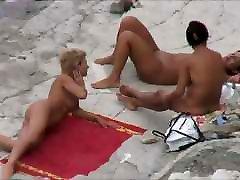 तीन महिलाओं के साथ नग्न न्यडिस्ट समुद्र तट पर
