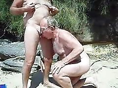 Old man sucks another man&039;s penis on a beach