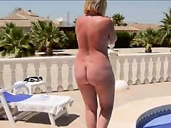A mature woman with a naked round feet festible walks by the pool