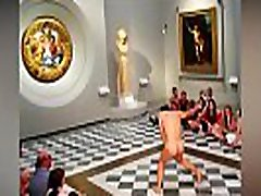 Barefoot naked man dances completely naked in a museum