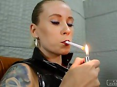 The hot girl showing wet panty smokes a cigarette and her sex slave licks her high heels.