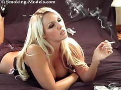The busty blonde boob biting videos smokes a cigarette. Her hot big tits make you horny!